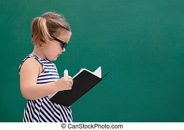Girl Reading Book Standing In Front Of Chalkboard