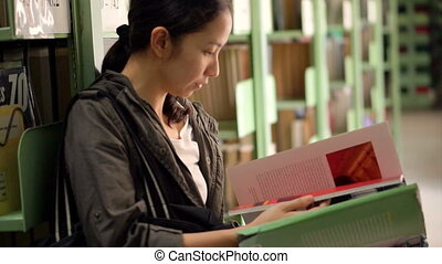 girl reading books at bookshelves