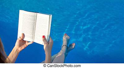 Girl reading by the swimming pool