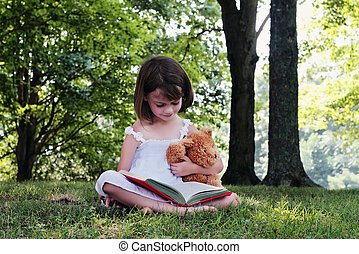 Girl Reading - Girl reading outdoors to her little teddy...