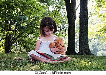 Girl Reading - Girl reading outdoors to her little teddy...