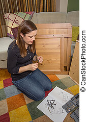 Girl reading instructions to assemble furniture - Girl with...