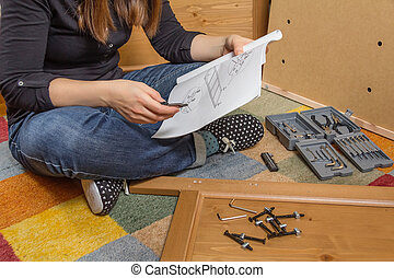 Girl reading instructions to assemble furniture - Closeup of...