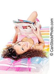 girl reading magazine on air mattress