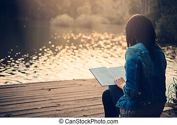 Girl reading on a pier