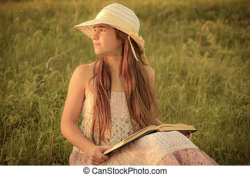 Girl reading the book on rural landscape at meadow