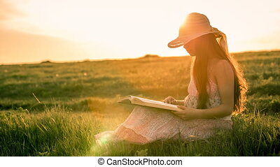 Girl reading the book on rural landscape at sunset -...