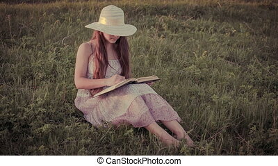 Girl reading the book on rural landscape, sepia toned -...