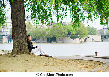 Girl reading under a tree near Seine