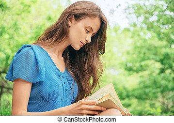 Girl reads a book outdoor