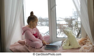 Girl reads a book to a toy bear while sitting on a...