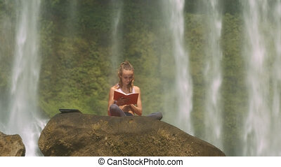 Girl Reads Book against Plants behind Waterfall Jets