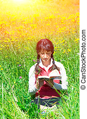Girl reads book sitting in a meadow