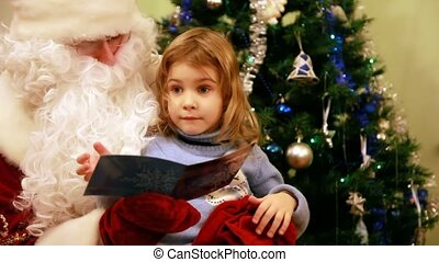 Girl reads in Santa Claus kneeling in front of the tree