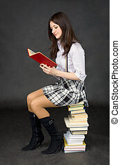 Girl reads the book, sitting on pile of books