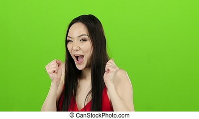 Girl received a big win, she is happy with her victory. Green screen. Slow motion