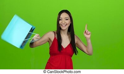 Girl received a gift, opens it and rejoices. Green screen. Slow motion