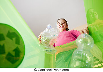 Girl holding plastic bottles for recycling, viewed from inside recycling bin. Copy space