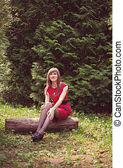 girl red dress in tights the woods sitting on a log
