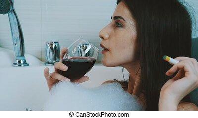 Girl relax in bath full of foam. Smoke electronic cigarette, drink red wine.