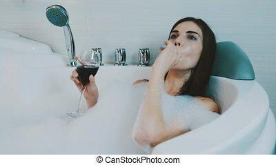 Girl relax in bath full of foam. Smoke electronic cigarette, steam, red wine.