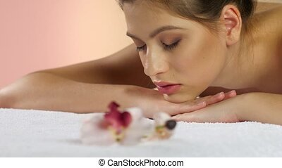 Girl relaxes after a massage lying on white towels. Studio -...