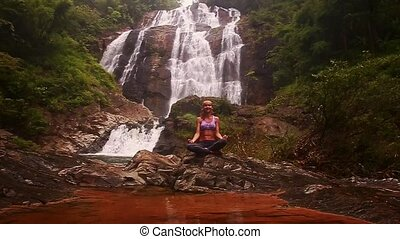 Girl Relaxes in Yoga Position behind Small Lake at Waterfall...