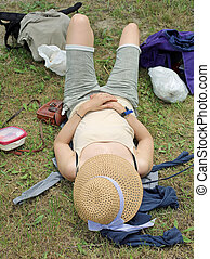 girl relaxes with a straw hat after picnic