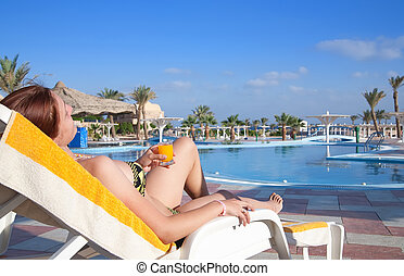 Girl relaxing against with orange juice at resort hotel