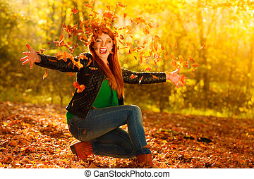 Girl relaxing in autumn park throwing leaves up in the air...