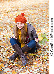 Girl relaxing in park on a fall day