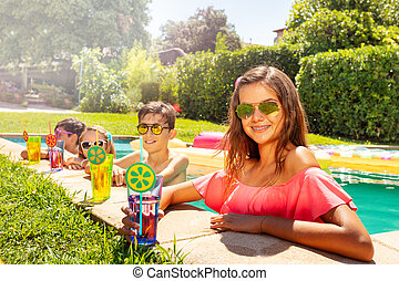 Girl relaxing in swimming pool with friends