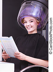 Girl relaxing reading magazine hairdryer by hairstylist in hair beauty salon