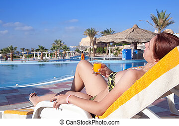 Girl relaxing with orange juice at resort hotel