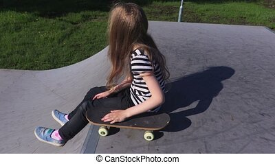 Girl relaxing with skateboard on ramp