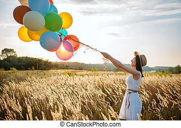 Girl releases a bunch of balloons into the sky