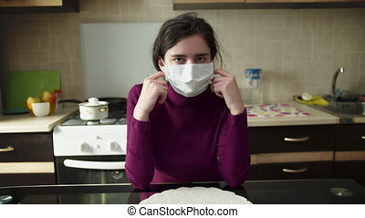 Girl removes a medical mask while sitting at home, in the background of the kitchen