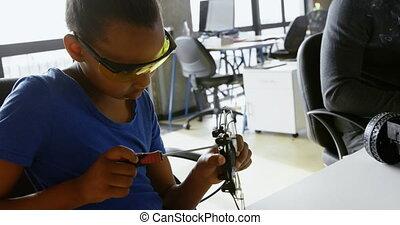 Girl repairing a drone at desk 4k