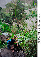 Girl resting after track on the stone and admiring spectacular green banana and sugarcane plants on the valley. Santo Antao island in Cabo Verde