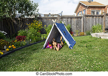 Girl resting in a tent on the grass in the garden