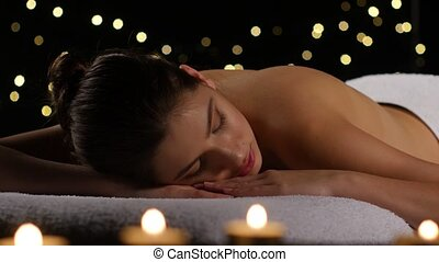 Girl resting in room with burning candles and dark...