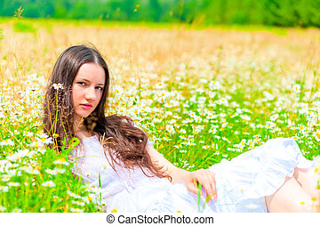 girl resting in summer field with flowers