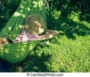 girl resting lying in a hammock