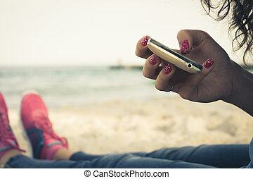 Girl resting on the beach and using a mobile phone