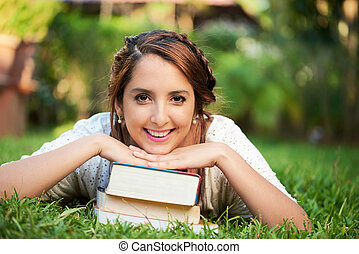 girl resting on top of books
