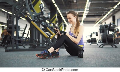 Girl Rests in Gym with Phone