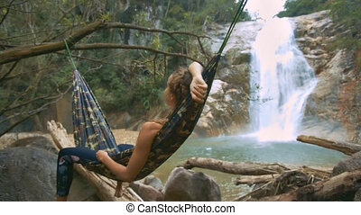 Girl Rests in Hammock Hung over Rocks by Waterfall
