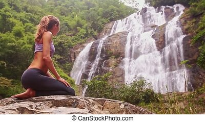 Girl Rests in Yoga Position near Foamy Waterfall Closeup