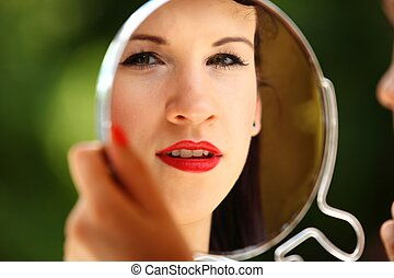 girl retro style applying make up looking at mirror indoor