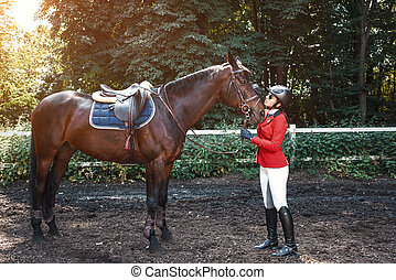 Girl rider and a horse posing in spring forest